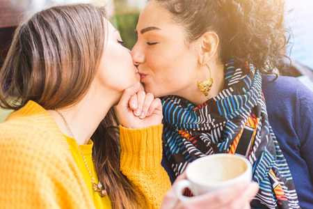 Foto de Lesbian couple kissing at a cafe. The young women are having a coffee together and give each other a passionate kiss. Candid situation with real people. Homosexuality and lifestyle concepts. - Imagen libre de derechos