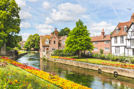 Foto de View of typical houses and buildings in Canterbury, England. Flowers and trees along the canal in summer. Postcard image on a sunny day. Architecture, nature and travel concepts. - Imagen libre de derechos