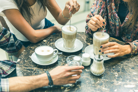 Foto de Multiracial group of friends at cafe together. Two women and a man at cafe, focus on glasses and cups, with coffee and cappuccino. Friendship and coffee culture concepts with real people models. - Imagen libre de derechos