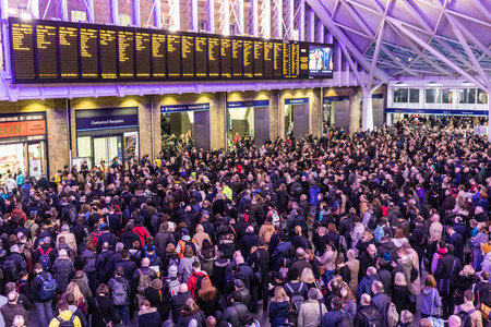 Foto de LONDON, UK - FEBRUARY 23, 2017: Crowded Kings Cross station in the city. Hundreds people waiting for the train, with delays and cancellations as Storm Doris lashes UK - Imagen libre de derechos