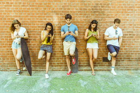 Foto de Group of friends using smartphone not interested in each other. Five persons leaning to a wall and looking at their own phone, ignoring friends. Technology and social media addiction in real life. - Imagen libre de derechos