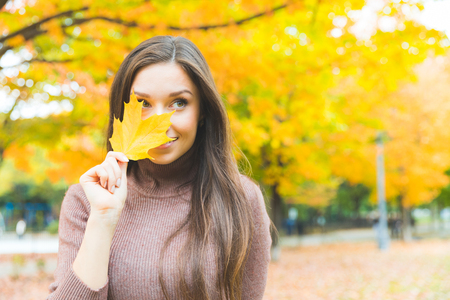 Foto de Portrait of a beautiful young woman hiding behind a yellow leaf. Smiling woman wearing turtleneck sweater with trees on background. Autumn season theme. - Imagen libre de derechos