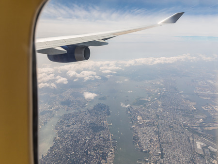 Foto de New York aerial view through airplane window. Beautiful panoramic view of Manhattan and Jersey city with plane engine and wing in foreground - Imagen libre de derechos