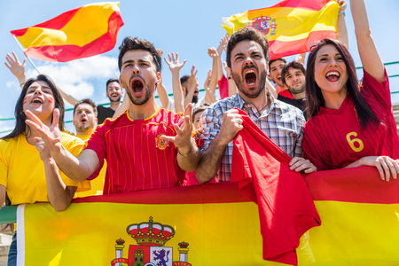 Photo for Spanish supporters cheering at stadium with flags. Group of fans watching a match and cheering team Spain. Sport and lifestyle concepts. - Royalty Free Image