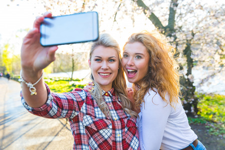 Photo for Two women taking a selfie at park in London. Two beautiful girls, lesbian couple or friends, having fun and bonding together on a sunny day. Homosexuality and lifestyle concepts. - Royalty Free Image