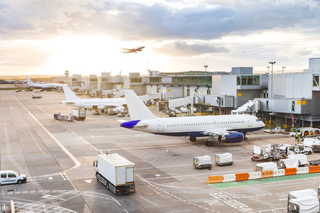 Photo for Busy airport view with airplanes and service vehicles at sunset - Royalty Free Image