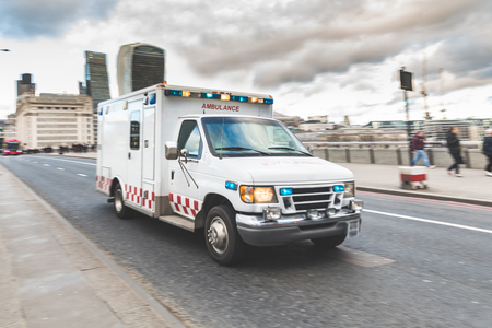 Foto de Emergency ambulance rushing on the street with emergency lights flashing in London city centre. Medical and emergency concepts, panning technique. - Imagen libre de derechos