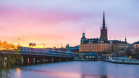 Foto de View of Stockholm old town and metro train at sunset. Typical scandinavian architecture and colors with pink and orange clouds. Travel and tourism concept in the capital city of Sweden. - Imagen libre de derechos