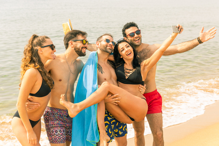 Foto de Happy friends taking a selfie on the beach in Barcelona. Multiracial group of best friends enjoying summer time together ready to take a swim. Happiness and friendship during a travel in Spain - Imagen libre de derechos