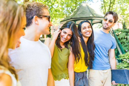 Photo pour Group of best friends at park talking and having fun. Multi ethnic people enjoying time together and laughing in London. Carefree and lifestyle concepts with real people - image libre de droit
