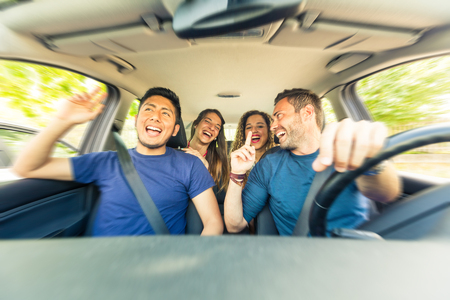 Photo pour Friends inside the car singing during a road trip . Multicultural group of friends leaving for vacations. Two men sitting on the front and two women on the back singing, laughing and having fun - image libre de droit