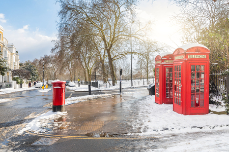 Foto de Red phone boxes in London with snow. Unusual view of the capital city covered by snow on a sunny and cold winter day. Travel and weather concepts - Imagen libre de derechos