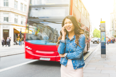 Photo pour Asian woman in London talking on the phone. Beautiful asian girl walking on the sidewalk, red double decker bus on background. Travel and tourism concepts - image libre de droit