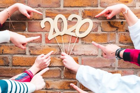 Photo pour Fingers pointing to new year 2020 sign - Teen friends holding a 2020 sign and celebrating new year - Holidays and culture concepts - image libre de droit