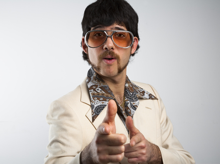 Photo pour Portrait of a retro man in a 1970s leisure suit and sunglasses pointing to the camera - image libre de droit
