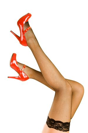 A pair of women's legs up in the air with red shoes and stockings.