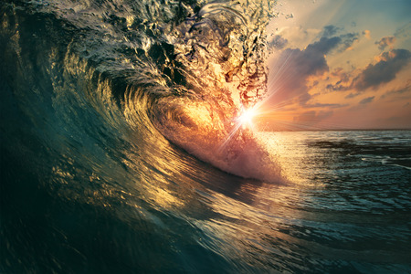 Foto de rough colored ocean wave falling down at sunset time - Imagen libre de derechos