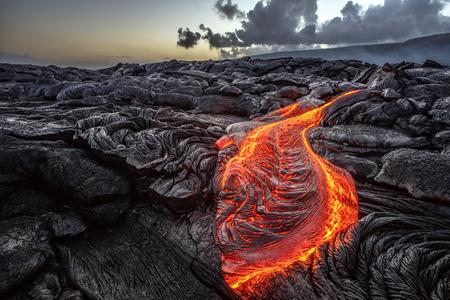 Foto de Red Orange vibrant Molten Lava flowing onto grey lavafield and glossy rocky land near hawaiian volcano with vog on background - Imagen libre de derechos