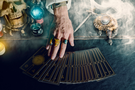 Photo pour Hand of fortune teller and tarot card on the table under candlelight. Dark tone. - image libre de droit