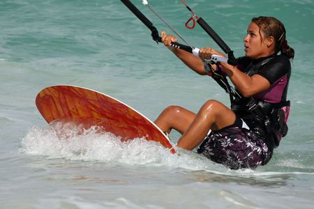 Young pretty girl in a wetsuit learns to kitesurf