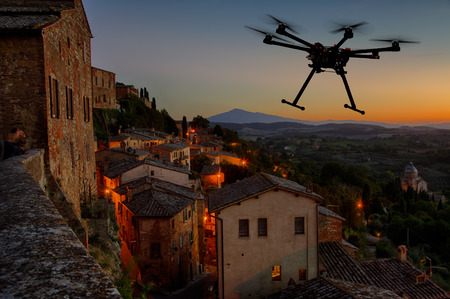 Foto de A silhouette of a flying drone with a dramatic sunset in the background in the skies of old European city - Imagen libre de derechos
