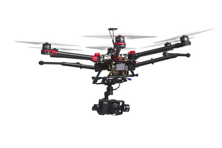 Foto de A flying helicopter with raised landing gears and a camera isolated on white background. Includes clipping path. - Imagen libre de derechos