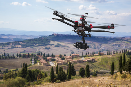 Foto de A flying helicopter with raised landing gears and a camera with blured hills of Tuscany in the background - Imagen libre de derechos
