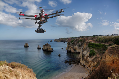 Foto de A drone with raised landing gears and a camera flying in beautiful cloudy skies along spectacular sea cliffs with a calm ocean in the background - Imagen libre de derechos