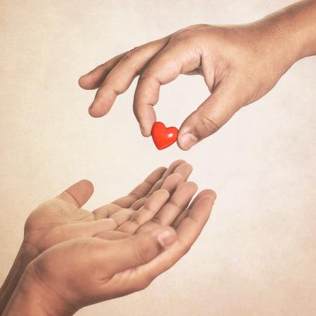 Photo pour Share your love (hand giving a heart in vintage style) - image libre de droit