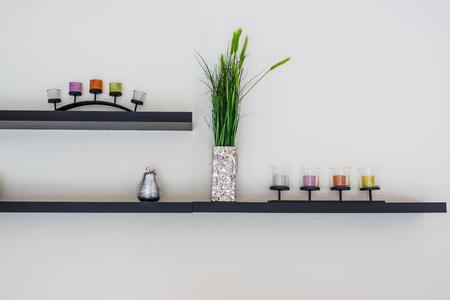 Photo pour Decorative candle with flower vase on wooden shelf. - image libre de droit