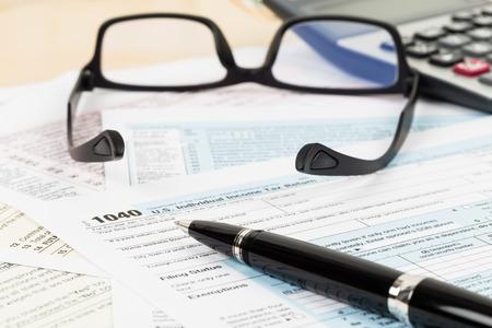 Photo pour Tax form with glasses, and calculator focus on pen - image libre de droit