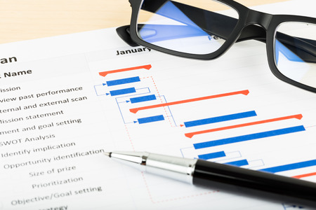 Foto de Project management and gantt chart with glasses and pen - Imagen libre de derechos
