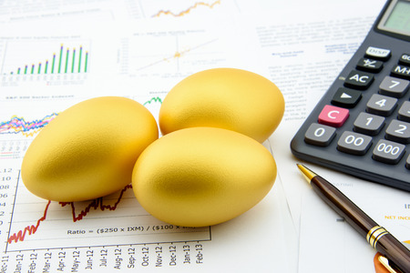 Photo pour Three golden eggs with a calculator on business and financial reports : Investment concept - image libre de droit