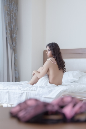 Sexy brunette young woman sitting on bed