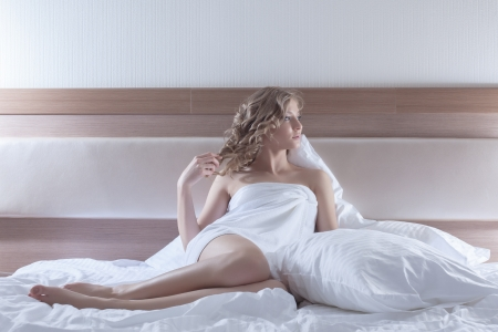 Full length portrait of sexy blonde woman sitting on bed