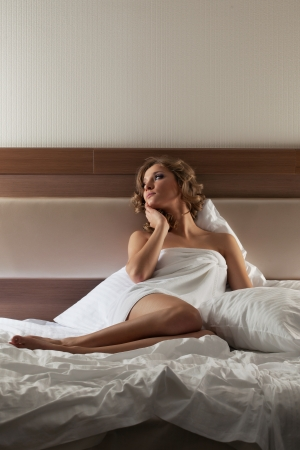 Portrait of pretty blonde woman sitting on bed