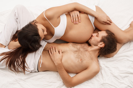 Photo for Man kissing belly of pregnant wife lying in bed - Royalty Free Image