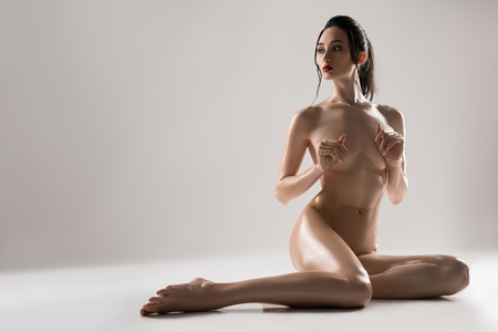 Foto de Gorgeous nude brunette sitting on the floor - Imagen libre de derechos