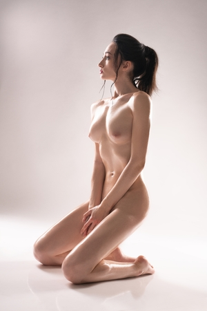 Photo for Nude brunette sitting on her knees shot - Royalty Free Image