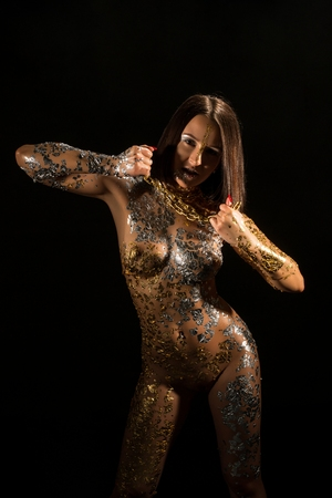 Photo pour Naked girl with gold bodyart and chain on her neck - image libre de droit