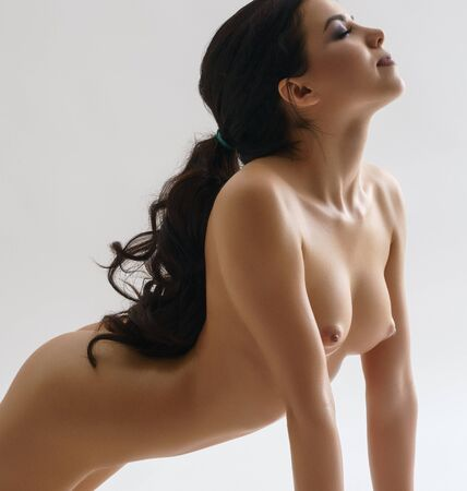 Foto per Long haired brunette shot naked staying on knees - Immagine Royalty Free