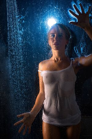 Photo pour Woman in wet t-shirt in shower view in the dark - image libre de droit