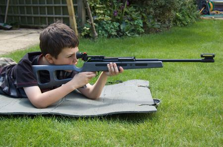 A young boy aims confidently with a target shooting air-rifle