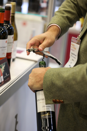 Photo for CRACOW POLAND - NOVEMBER 16 2017: International Wine Trade Fair ENOEXPO in Cracow. Man's Hands Opening Wine Bottle with Corkscrew  - Royalty Free Image