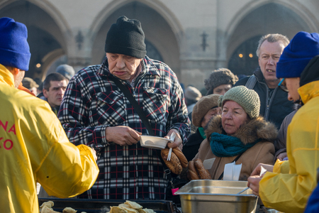 Foto de Cracow, Poland - December 17, 2017:   Christmas Eve for poor and homeless on the Main Square in Cracow. Every year the group Kosciuszko prepares the greatest eve in the open air in Cracow. Poland - Imagen libre de derechos