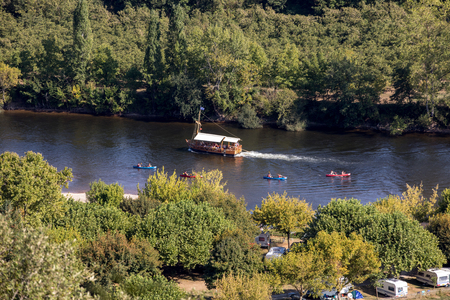 Photo pour La Roque-Gageac, Dordogne, France - September 3, 2018: Canoeing and tourist boat, in French called gabare, on the river Dordogne at La Roque-Gageac, Aquitaine, France - image libre de droit