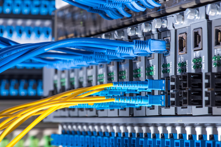 Photo for Fiber Optic cables connected to an optic ports and Network cables connected to the ports - Royalty Free Image