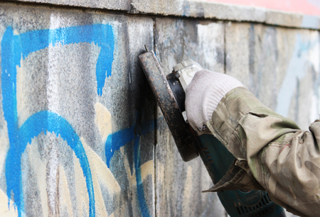 Foto de Removal of graffiti on a concrete wall of an underground passage with the help of a angle grinder. - Imagen libre de derechos