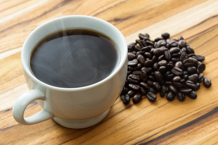 fresh cup of steaming coffee with whole beans over a teak wood background