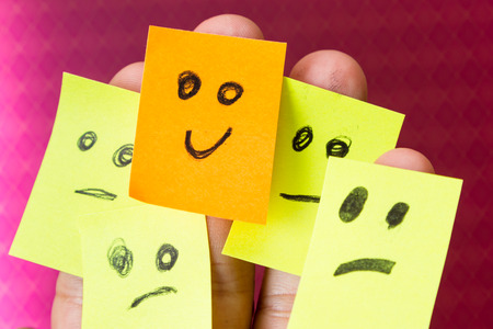 Photo for concept for optimism with paper faces on multiple fingers one with a happy good attitude - Royalty Free Image